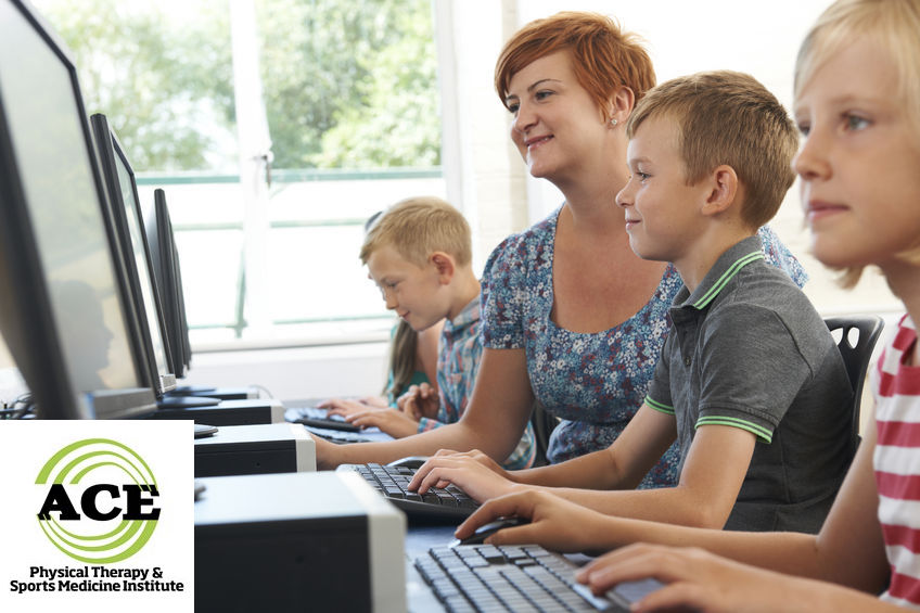 46116695 - male elementary pupil in computer class with teacher