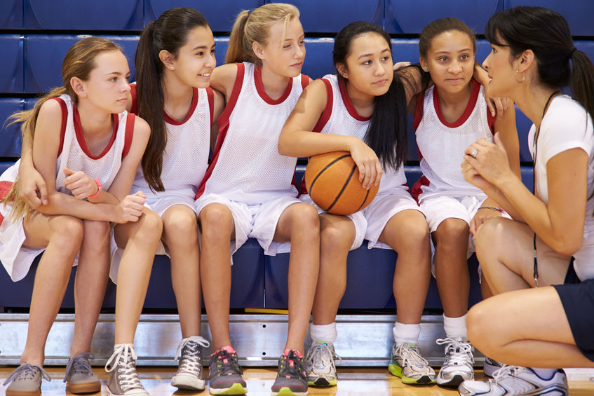 33478109 - coach of female high school basketball team gives team talk