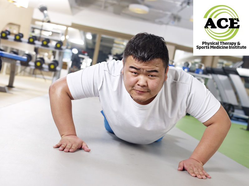 24461735 - an overweight young man doing push-ups with sweating face